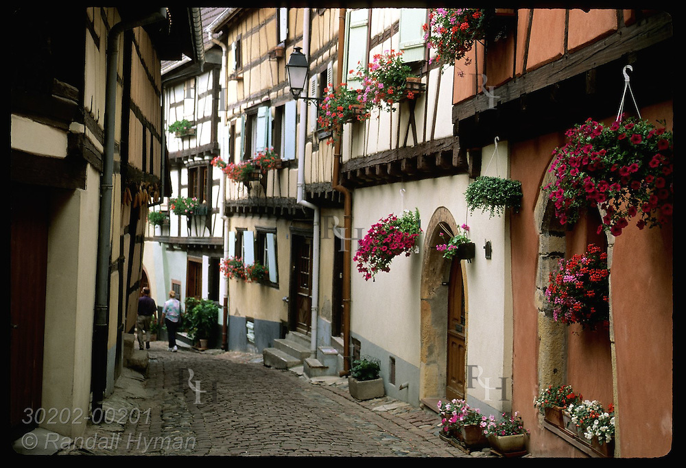 Couple walks down narrow street lined with old half-timbered homes; (h) Eguisheim, Alsace. France