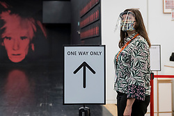 © Licensed to London News Pictures. 24/07/2020. LONDON, UK. A Tate staff member wearing a facemask next to a direction sign. Press preview ahead of the reopening of Tate Modern on 27 July after the easing of coronavirus pandemic lockdown restrictions by the UK government.  Visitors will need to book timed tickets online and follow one-way routes around the gallery space along with observing social distancing rules.  Photo credit: Stephen Chung/LNP