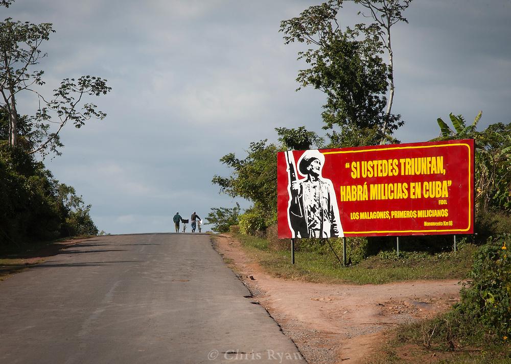 Political billboard and men walking bikes, Vinales Valley, Cuba