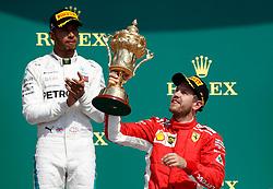File photo dated 08-07-2018 of Ferrari's Sebastian Vettel (right) celebrates winning the 2018 British Grand Prix alongside Mercedes' Lewis Hamilton.