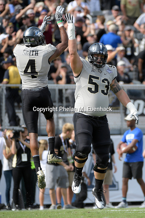 Central Florida wide receiver Tre'Quan Smith (4) celebrates with offensive lineman Tyler Hudanick (53) after scoring a touchdown on a 50-yard reception during the first half of the American Athletic Conference championship NCAA college football game against Memphis Saturday, Dec. 2, 2017, in Orlando, Fla. (Photo by Phelan M. Ebenhack)