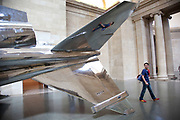 "Harrier and Jaguar, a grand scale art installation by artist Fiona Banner in the main space Duveen Galleries in Tate Britain gallery. The two stripped down decommissioned fighter jets dominate these great spaces. A Harrier Jump Jet, suspended from the ceiling painted with feint feathers, and the Jaguar, stripped of all ot's paint and polished to a gleaming high silver. Says the artist: ""I remember long sublime walks in the Welsh mountains with my father, when suddenly a fighter plane would rip through the sky , and shatter everything. It was so exciting, loud and overwhelming. It would really take our breath away. The sound would arrive from nowhere, all you would see was a shadow and then the plane was gone. At the time the Jump Jets were at the cutting edge of technology but to me they were like dinosaurs, prehistoric, from a time before words."""