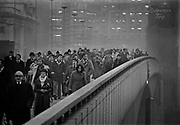 Commuters at 5.30pm leaving the city crossing London Bridge, winter 1976. London Bridge, which opened to traffic in 1973, is a box girder bridge built from concrete and steel. This replaced a 19th-century stone-arched bridge, which in turn superseded a 600-year-old medieval structure. This was preceded by a succession of timber bridges, the first built by the Roman founders of London. Coming and Going is a project commissioned by the Museum of London for photographer Barry Lewis in 1976 to document the transport system as it is used by passengers and commuters using public transport by trains, tubes and buses in London, UK.