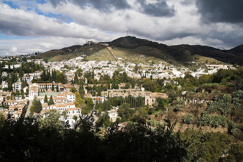 View of the historic whitewashed buildings and surrounding hills below La Alhambra in Granada, Andalusia, Spain.