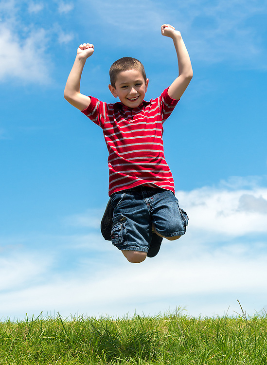 6 years old boy jumping very happy in a park during summertime