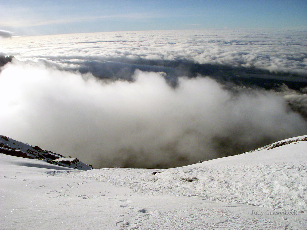 A view from the summit of Mt. Kilimanjaro at 19,000 plus feet, with clouds stretching out below and glaciers in view.