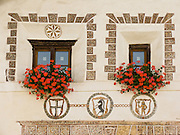 """Flowers and scraffiti frame windows in Scuol, Engadine, Switzerland, the Alps, Europe. Scuol (or Schuls) is the terminal station of the """"Rätische Bahn"""" (RhB), at 1244 meters or 4081 feet elevation in Graubünden canton. The Swiss valley of Engadine translates as the """"garden of the En (or Inn) River"""" (Engadin in German, Engiadina in Romansh, Engadina in Italian)."""