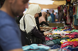 June 14, 2018 - Gaza City, The Gaza Strip, Palestine - Palestinians shop in a market before the holiday of Eid al-Fitr in the Jabalia camp the northern Gaza Strip on June 14, 2018. Eid al-Fitr is the end of Ramadan for Muslims when believers refrain from eating, drinking, smoking and sexual activities from dawn until dusk. (Credit Image: © Mahmoud Issa/Quds Net News via ZUMA Wire)