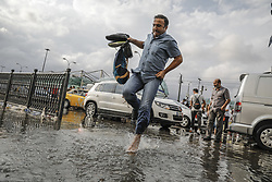 August 29, 2017 - Istanbul, Turkey - A man tip toes barefoot across a street. Heavy rain in Turkey's biggest city cause substantial flooding on roads and in its Metro network. (Credit Image: © Can Erok/Depo Photos via ZUMA Wire)