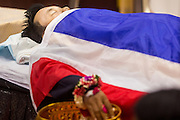 19 FEBRUARY 2014 - BANGKOK, THAILAND: The bathing rites for Police Senior Sgt-Major Phianchai Pharawat, 45. Bathing rites are the first step in Buddhist funeral ritual. Phianchai was killed by anti-government protestors Tuesday during an altercation between protestors and police. Four people were killed and more than 60 hospitalized as a result of the fighting. Anti-government protestors aligned with Suthep Thaugsuban and the People's Democratic Reform Committee (PRDC) attacked police officers who tried to clear protestors out of sites they've occupied since January.    PHOTO BY JACK KURTZ