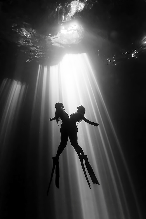 Mexico, Quintana Roo. Two freedivers are rising together into the sunrays at cenote KinHa.