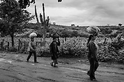 Women walk along a road in the rural area of Guaribas, Piauí state, one of the poorest regions of Brazil. For most of the population, getting food and water is a daily challenge. With no alternative income, many families migrate to large cities in southeastern Brazil in search of work.<br /> Guaribas was chosen in 2003 to be the pilot city for the first social welfare program of President Lula da Silva's government, which later became the Bolsa Família, one of the largest anti-poverty programs in the world.