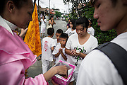 Onlookers receive blessings during street procession.The origins of the festival date back to 1825, when a traveling Chinese opera company came to Phuket to perform for the miners there. An epidemic broke out and as the members of the company fell sick, they adhered to a vegetarian diet to honor two of the Emperor Gods, Kiew Ong Tai Teh and Yok Ong Sone Teh. When they became well again shortly thereafter, the people of Phuket followed the company's example - and have celebrated the festival ever since to bring good luck to their communities.