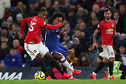Forward Odion Ighalo of Manchester United  and Midfielder Willian of Chelsea compete for the ball during the English Premier League match between Chelsea and Manchester United, Monday, Feb. 17, 2020, at Stamford Bridge, in London, United Kingdom. Manchester United defeated Chelsea 2-0.  (Mitchell Gunn/Image of Sport)