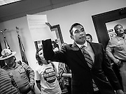17 OCTOBER 2013 - PHOENIX, AZ:  JOSE BETO SOTO, field director of Citizens for a Better Arizona, waves a letter he sent to the Attorney General the office of the Arizona Attorney General shortly before he was arrested during a protest in the offices of Arizona Attorney General. About 100 people came to the office of Arizona Attorney General Tom Horne to protest the decision by Horne to sue community colleges in Maricopa County that charge DREAM Act students who are residents of Arizona out of state tuition rather than in state resident tuition. Nearly 10 people were arrested in a planned civil disobedience during the protest.    PHOTO BY JACK KURTZ