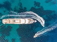Aerial view of jet ski driving around luxurious yacht in the mediterranean sea, Mikonos island, Greece.
