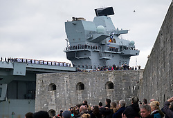 © Licensed to London News Pictures. 16/11/2019. Portsmouth, UK.  Crowds watch as HMS Prince of Wales, the Royal Navy's second Queen Elizabeth-class aircraft carrier, towers above the Round Tower as she sails into Portsmouth Naval Base for the first time this afternoon, 16th November 2019. The £3.1 billion warship has been undergoing eight weeks of sea trials in the Moray Firth. Photo credit: Rob Arnold/LNP