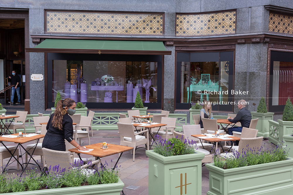 On the day that covid pandemic guidelines for shoppers in England mean that the wearing of face coverings in shops becomes mandatory, a waitress wearing a face covering wipes down table surfaces near customers outside Harrods's in Knightsbridge, on 24th July 2020, in London, England.