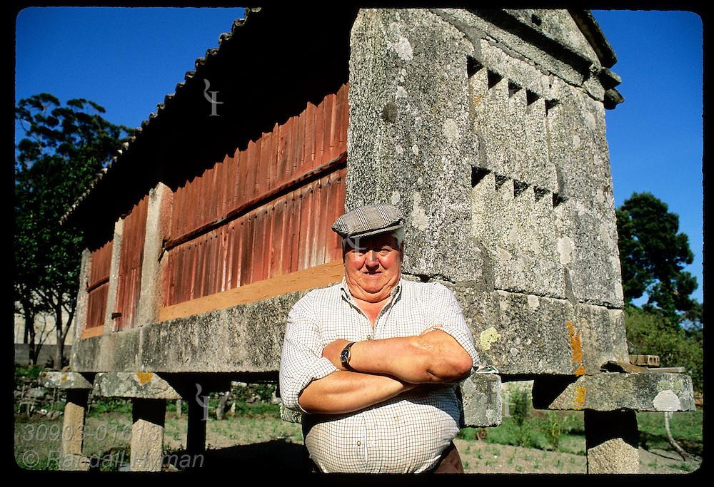 Farmer Juan Carlotta Abal poses by his family 'hórreo,' a traditional stone granary on stilts near Combarro, Galicia, Spain