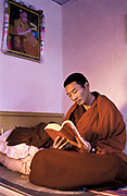 Tibetan buddhist monk Dongyu, reads  the Buddha's teachings under the watchful smile of the  present Dalai Lama in his small but well equiped and furnished living space  comprising of a living room / bedroom and a small wood fired kitchen, within the  300 years old walls of Atsog Monastery, Xinghai County, Qinghai Province, China.