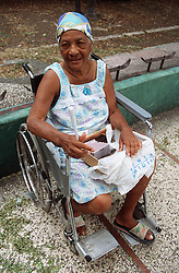 Woman with disability; who is wheelchair user; selling peanuts on street in Havana; Cuba,