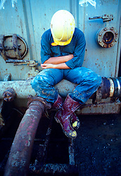 Man in a yellow hard hat resting on a pipe