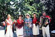 Folk group accordion music performing outside Yalta, Crimes, Russia in 1997 woman tourist posing with performers