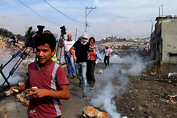 November 11, 2016 - Nablus, West Bank, Palestine - Palestinian protesters run for cover from tear gas canister fired by Israeli security forces during clashes following a demonstration against the expropriation of Palestinian land by Israel on November 11, 2016 in the village of Kfar Qaddum, near Nablus, in the occupied West Bank. (Credit Image: © Mohammed Turabi/ImagesLive via ZUMA Wire)