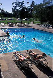 Stock photo of a man and woman relaxing beside a pool while the children swim