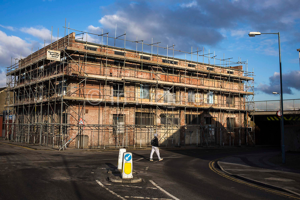 A man walks past a large derelict building called The Garage, which has become a building site on Boundary Road, Middlesborough, England, UK.  The old building has been fenced off an covered in scaffolding.