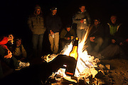 A young man drinks beer at night around a campfire in the San Rafael Swell, Utah.