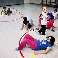 Nederland, Amsterdam , 19 november 2013.<br /> Het project Vet fitte kids, voor kinderen met overgewicht.<br /> De cursus wordt onder de begeleding van een fysiotherapeut gegeven aan de Amstelschool in Amsterdam Noord.<br /> Op de foto: Leroy (staand) is moe.<br /> Op de foto specifieke gymles<br /> Foto:Jean-Pierre Jans