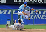 April 30, 2008:  Shortstop Mike Aviles #30 of the Kansas City Royals leaps over base runner Travis Snider #45 of the Toronto Blue Jays after making a throw to first base for a double play during the seventh inning at Kauffman Stadium in Kansas City, Missouri.  The Royals defeated the Blue Jays 8-6...