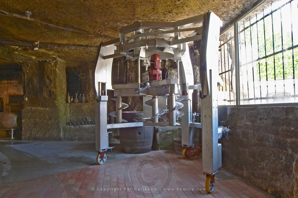 The underground winery and cellar in an old stone quarry, a curious machine with screws for making pigeage pressing the cap of grape skins and pips down into the must Chateau Belair (Bel Air) 1er premier Grand Cru Classe Saint Emilion Bordeaux Gironde Aquitaine France