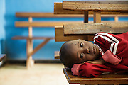 Lacine, 4, who suffers from malaria and diarrhea, lies on a bench as he waits with his family at the Libreville health center in Man, Cote d'Ivoire on Wednesday July 24, 2013.