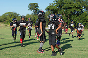 Kids warm up before football practice with Truth, a youth sports organization founded by Deion Sanders that is sponsored by Under Armour, at the Prime Prep Academy campus in Dallas, Texas on August 6, 2014. (Cooper Neill for The New York Times)
