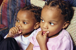 Portrait of young twin girls sitting together,
