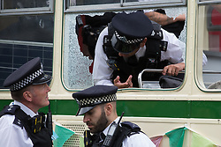 London, UK. 31st August, 2021. Metropolitan Police officers converse through the broken window of a vintage bus used by environmental activists from Extinction Rebellion to block a road junction to the south of London Bridge on the ninth day of their Impossible Rebellion protests. Extinction Rebellion are calling on the UK government to cease all new fossil fuel investment with immediate effect.