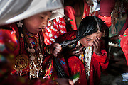 Fifteen year-old Ikhbal has been married for two months. Today is the veil ceremony, where she will exchange her childhood crimson veil for a married woman's white headdress. She struggles and cries as the older women around her get ready to fasten the white veil on her head..The Kyrgyz settlement of Ech Keli, above Chaqmaqtin lake, Er Ali Boi's camp...Trekking through the high altitude plateau of the Little Pamir mountains, where the Afghan Kyrgyz community live all year, on the borders of China, Tajikistan and Pakistan.