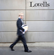 business man walks lovells office in suit and glasses with documents