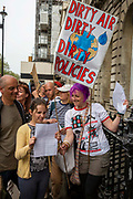Surrounded by Police Rifat and Claire with their daughter Amelie from Bishop's Stortford join Extinction Rebellion for the first time. They have arrived at 1 Parliament street and wait for access inside to hand a letter to their MP. They along with other demonstrators gather in Parliament Square outside the House of Commons ready to invite their local MP's to a People's Assembly on the climate and ecological emergency.  Westminster London, United Kingdom. Extinction Rebellion is a political movement with the main aim to avert climate breakdown, minimise human extinction and stop ecological collapse using non violent resistance.