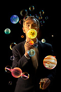 Color photograph of Bill Nye the Science Guy for PBS. Blowing bubbles into the planets of our solar system.