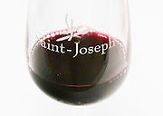 Detail of a red wine glass with Saint Joseph. Against a white background.  Domaine Eric et Joel Joël Durand, Ardeche, Ardèche, France, Europe