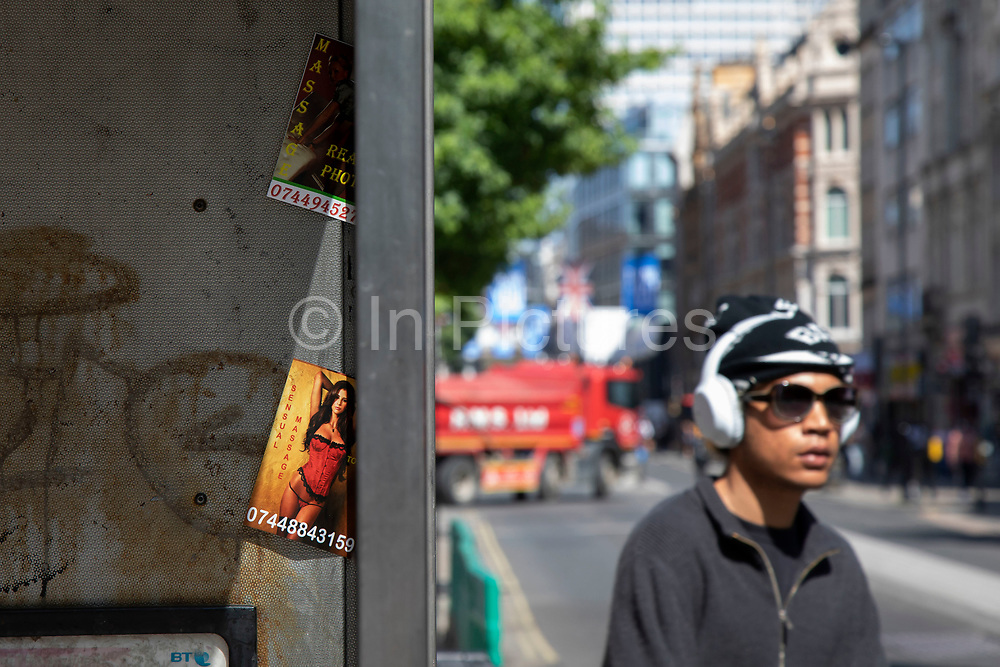People passing a public telephone box which has sex cards tacked up inside on 22nd <br /> June 2020 in London, United Kingdom. These advertising cards for prostitutes are how people advertise for sexual services under the guise of other services like massage for example.