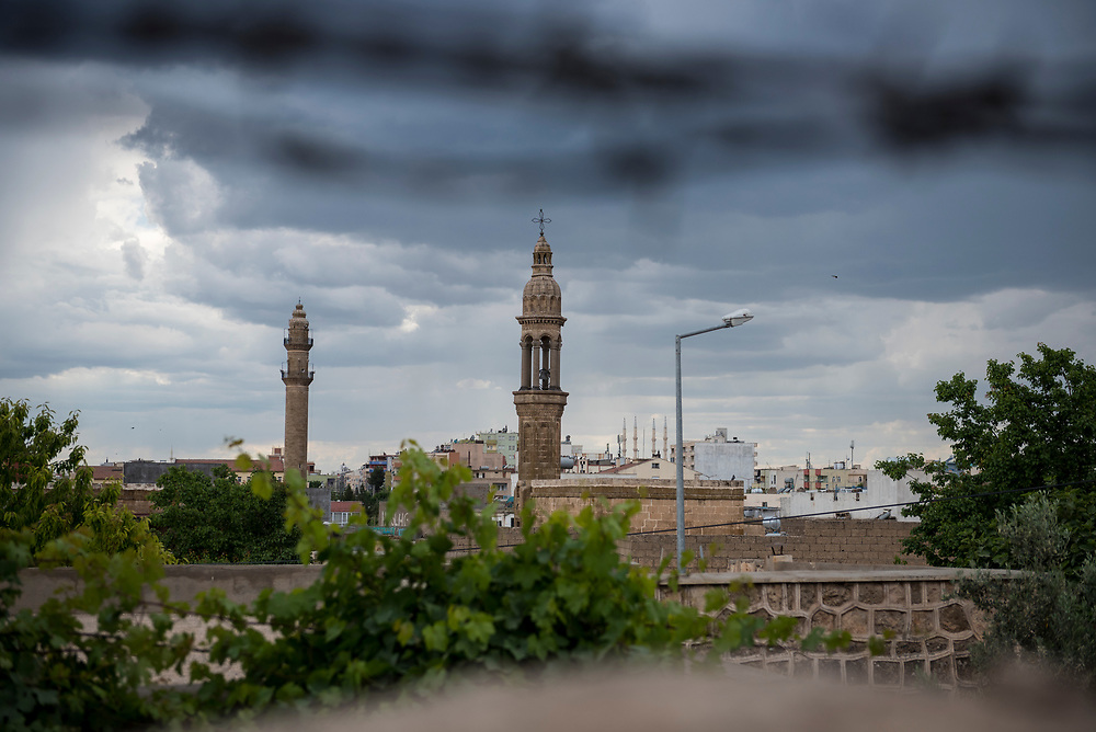 The bell tower of a Syriac Christian church, topped with a cross, rises above the skyline of Midyat, Turkey. On the left is the minaret of a mosque. At the top of the photo, out of focus, is barbed wire.