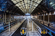 Railway trains waiting at platforms of Liverpool Street station, London, United Kingdom.  Liverpool Street station was opened in 1874 and is now the third busiest railway station in London.