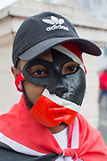 A young man wearing a coloured face mask during the Notting Hill Carnival on the 27th August 2018 in London in the United Kingdom. The Notting Hill Carnival is an annual event held over two days of the August Bank Holiday weekend. It has taken place in London since 1966 on the streets of Notting Hill, in the Royal Borough of Kensington and Chelsea and the City of Westminster.