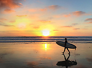 Surfer with surfboard waking along beach at sunset in Del Mar, CA.
