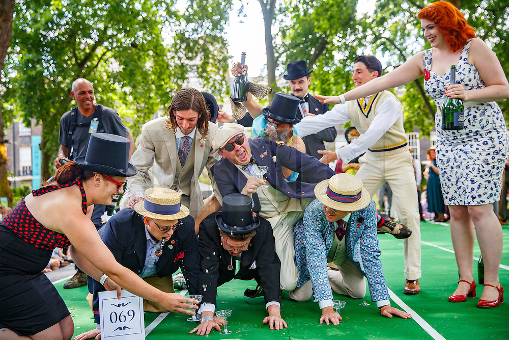 © Licensed to London News Pictures. 11/07/2015. London, UK. Competitors forming a 'human champagne pyramid' at The Chap Olympiad in Bedford Square, London on July 11, 2015. The Chap Olympiad is a light-hearted social sporting event aimed at revisiting the fashions and pastimes of the polite aspects of 1920's to 1950's England. Photo credit: Tolga Akmen/LNP