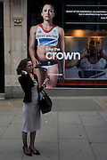 A woman stands beneath the inspiring image of Team GB gold medallist heptathlete Jessica Ennis which adorns the exterior of the Adidas store in central London's Oxford Street, during the London 2012 Olympic Games. The ad is for sports footwear brand Adidas and their 'Take The Stage/Crown' campaign which is viewable across Britain and to Britons who have been cheering these athletes who have been winning medals in numbers not seen for 100 years. Their heroic performances have surprised a host nation who until the victories, were largely anti-Olympics - now adoring their darling Ennis and her good looks.